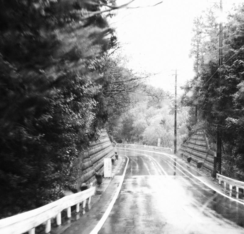 濡れた路面と山の道